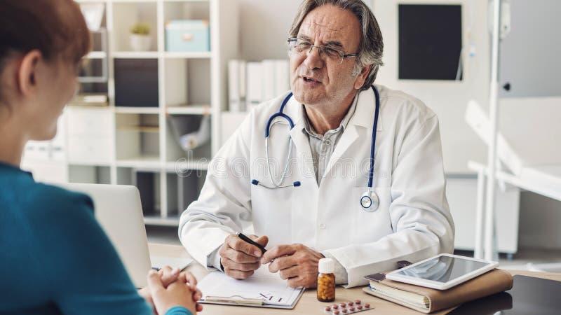 De arts en de patiënt bespreken bij kliniek royalty-vrije stock afbeeldingen
