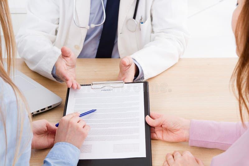 De arts en de patiënt bespreken iets, handen bij de lijst Medische Verzekering Doc.-zitting in kabinet Mens in witte eenvormig royalty-vrije stock afbeelding