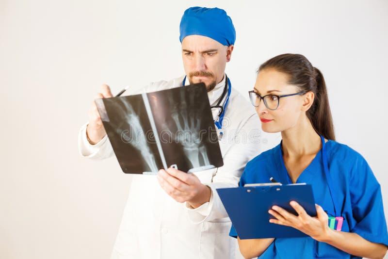 De arts en de verpleegster bekijken het resultaat van de Röntgenstraal, schrijft de arts de behandeling voor, schrijft de verplee royalty-vrije stock afbeeldingen