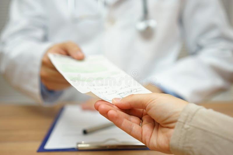De arts geeft een voorschrift aan een vrouwelijke patiënt stock fotografie