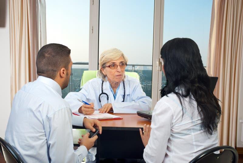 De arts geeft medisch adviezen aan paar royalty-vrije stock foto