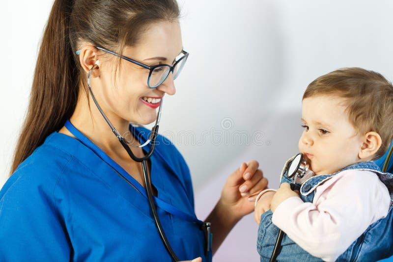 De arts glimlacht bij het kind terwijl hij met de stethoscoop speelt royalty-vrije stock fotografie