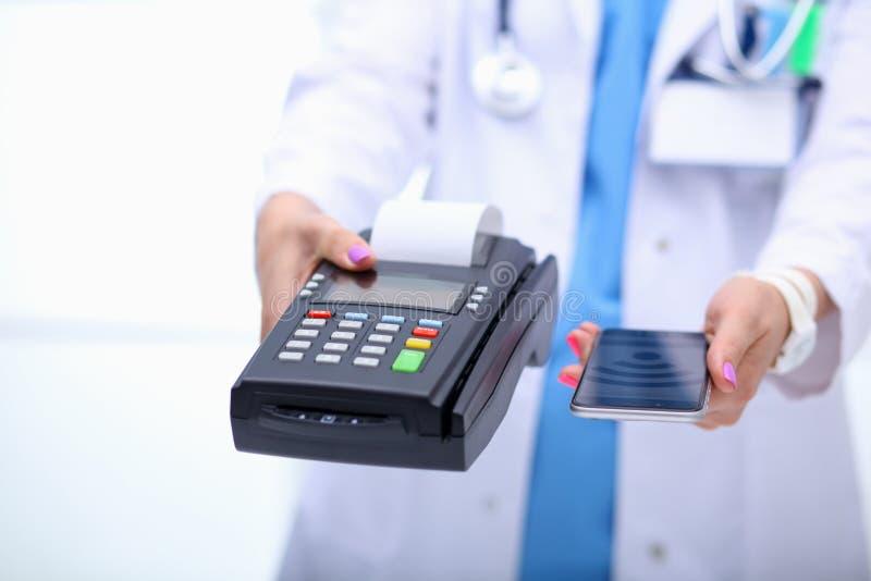 De arts houdt betalingsterminal in handen Het betalen voor gezondheidszorg Arts royalty-vrije stock afbeeldingen