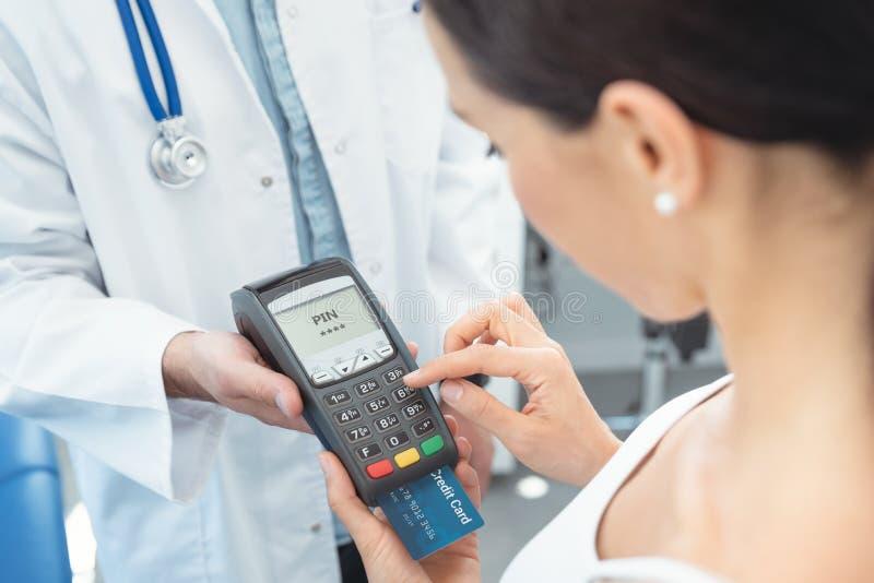 De arts houdt betalingsterminal in handen stock afbeelding