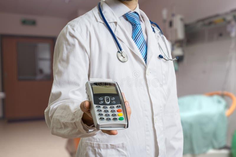 De arts houdt betalingsterminal in handen Het betalen voor gezondheidszorg royalty-vrije stock foto's