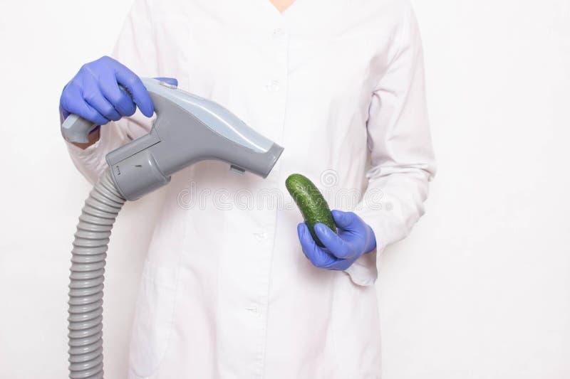 De arts houdt een komkommer dichtbij de stofzuiger op een witte achtergrond, het concept stijgende penis bij mensen met a royalty-vrije stock fotografie