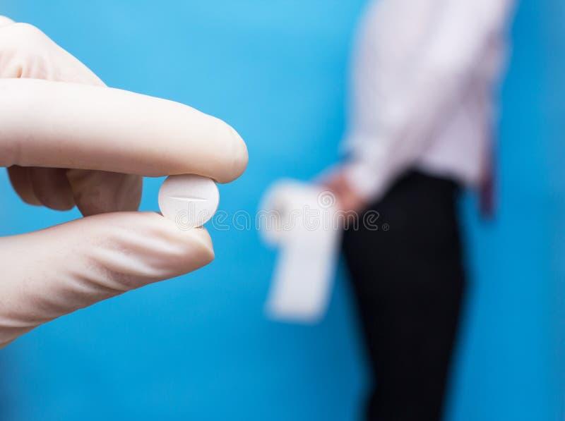 De arts houdt pillengeneeskunde voor diarree, bevindt een mens zich op de achtergrond en houdt toiletpapier, behandeling van indi stock foto