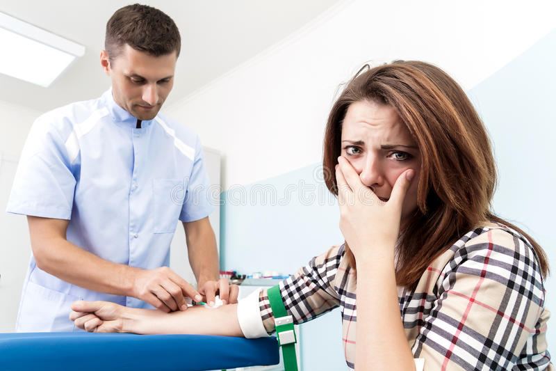 De arts maakt de patiënt tot een injectie van een jonge vrouw jong meisje bang van injectie royalty-vrije stock afbeeldingen