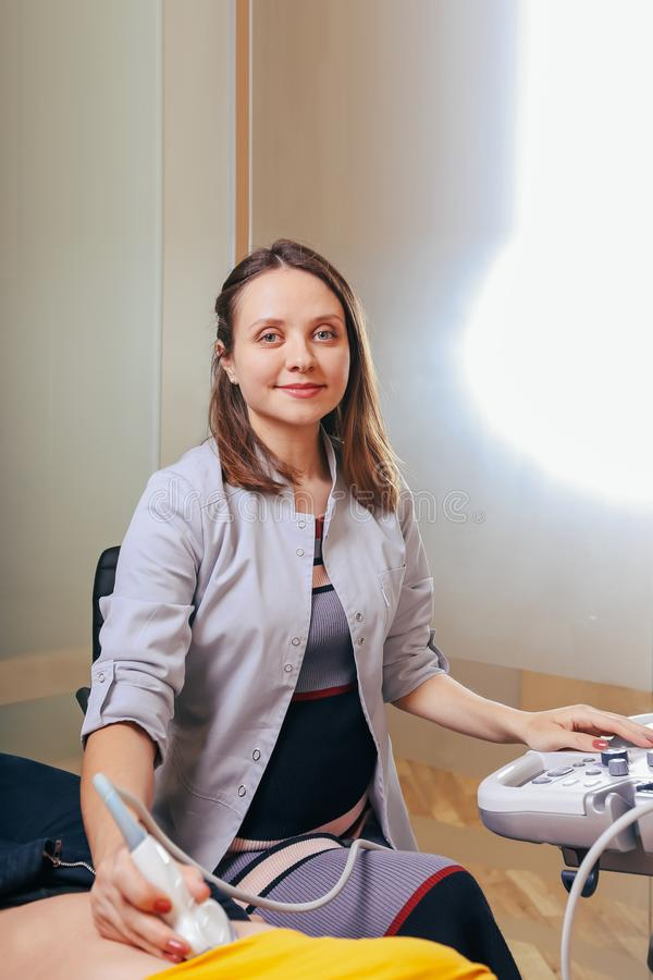 De arts maakt de geduldige vrouwen tot buikultrasone klank Ultrasone klankscanner in de handen van een arts stock afbeelding