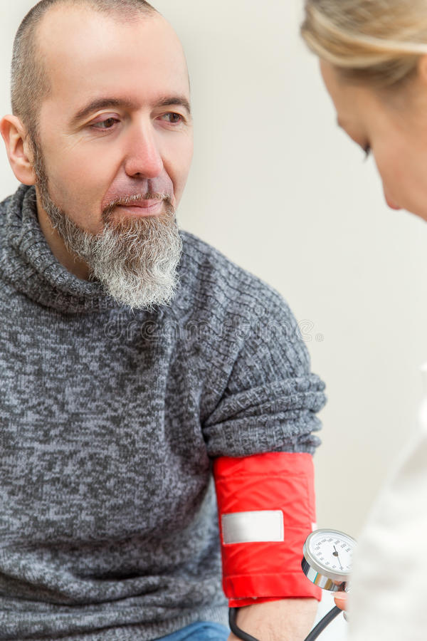 De arts meet de bloeddruk stock foto