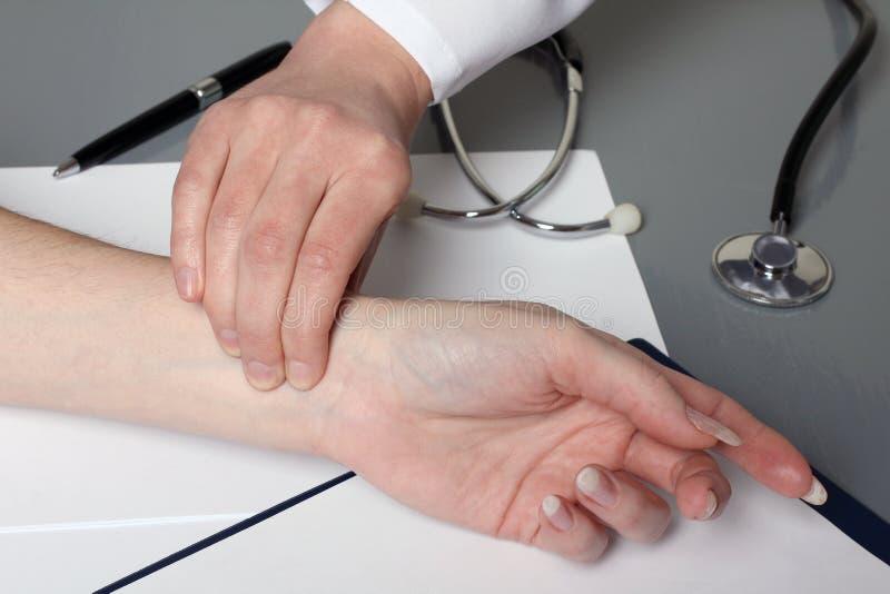 De arts meet de impuls van de patiënt stock afbeeldingen