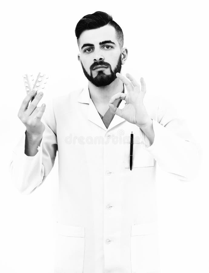 De arts met baard houdt pillenblaren en toont o.k. teken stock afbeeldingen