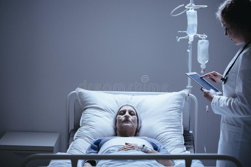 De arts met tablet naast bed met stervend bejaarde met kan royalty-vrije stock foto