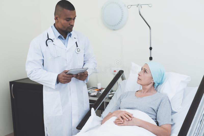 De arts ondervraagt de vrouw Een vrouw ondergaat rehabilitatie na kankerbehandeling stock foto's