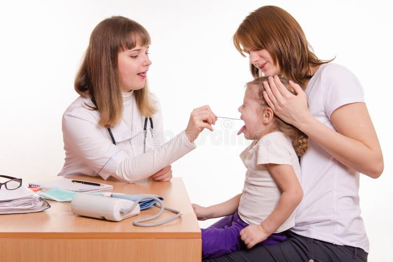 De arts onderzoekt de keel van een kindzitting op handen van moeder stock fotografie