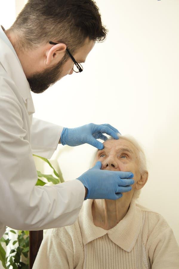 De arts onderzoekt de ogen, bindvlies zeer oude vrouw de artsengeriater tijdens de test royalty-vrije stock afbeeldingen