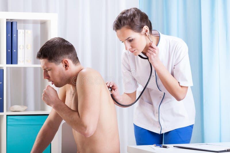 De arts onderzoekt een zieke patiënt stock afbeeldingen