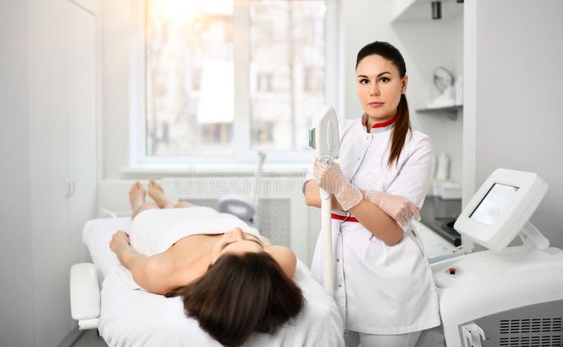 De arts-schoonheidsspecialist in witte toga met een medisch apparaat is bereid om kosmetisch procedur voor een patiënt in schoonh stock foto's