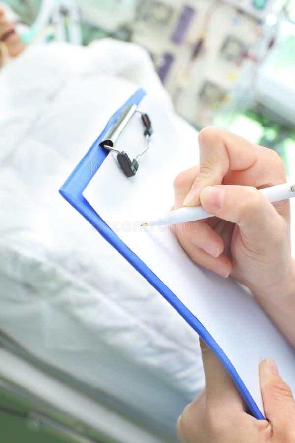 De arts schrijft op de afdeling van de klembordintern verpleegde patiënt stock afbeeldingen