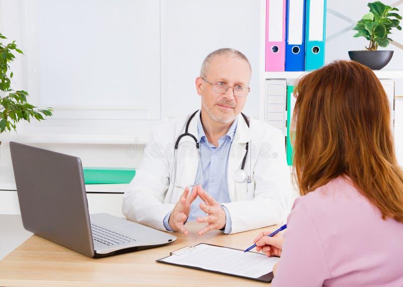 De arts spreekt met vrouwenpatiënt en zit in medisch bureau Mens in witte eenvormig Medische Verzekering De ruimte van het exempl royalty-vrije stock foto