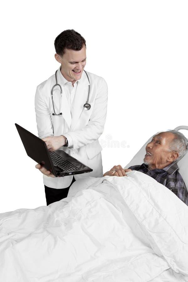 De arts toont laptop aan bejaarde mannelijke patiënt stock afbeelding