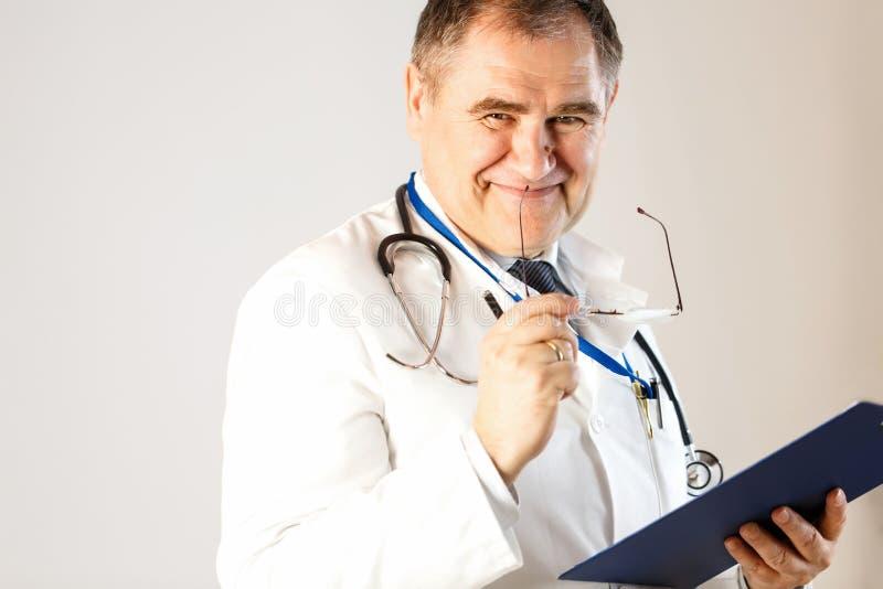 De arts van geneeskunde glimlacht, houdend glazen en een omslag voor verslagen stock afbeelding