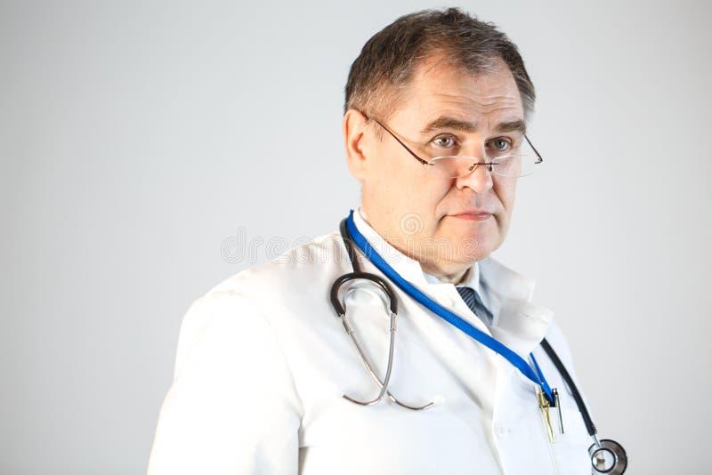 De arts verheugt zich op, duwend zijn glazen het uiteinde van zijn neus, een stethoscoop en een kenteken die van zijn hals hangen royalty-vrije stock foto