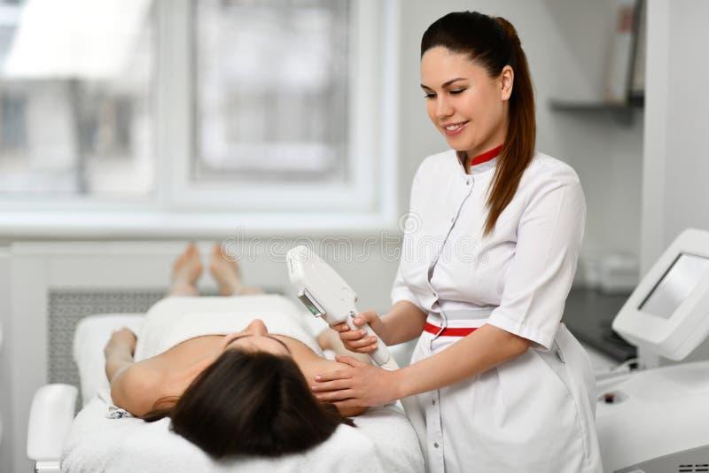 De arts voert een kosmetische procedure aangaande het gezicht van de patiënt met medische apparatuur uit en heeft een pret babbel royalty-vrije stock foto's