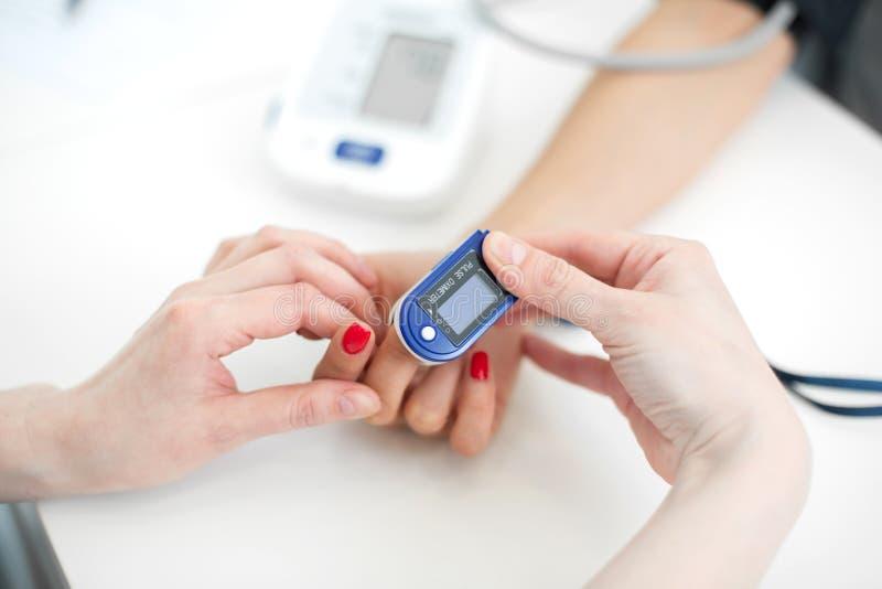 De arts zet op de sensor die de impuls en de zuurstof in het bloed op de vinger van de patiënt meten stock afbeelding