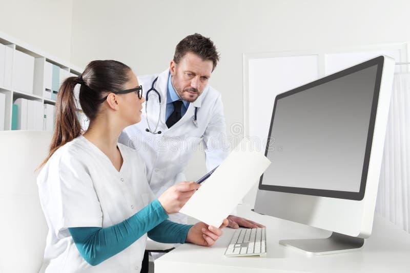 De artsen met verpleegster die medische dossiers, concept van raadplegen kijken stock foto's