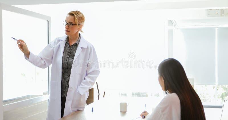 De artsen of de wetenschappers onderwijzen en verklaren studenten en p stock afbeeldingen