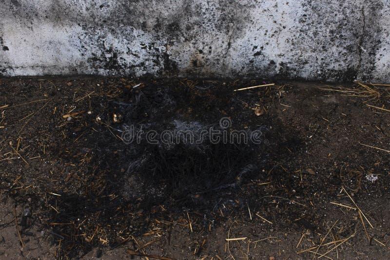 De as na brandwond het gras en de houten spaanders eindigt, naast de huismuur royalty-vrije stock afbeelding