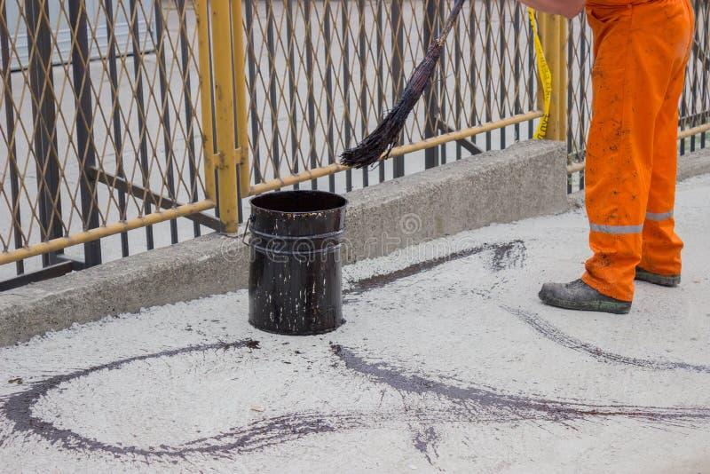 De asfaltarbeider past kopspijkerlaag (Bitumenemulsie) met een bezem 4 toe royalty-vrije stock foto