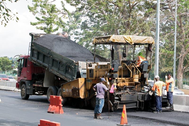 De asfaltmachine zet een nieuwe laag op de weg stock afbeelding