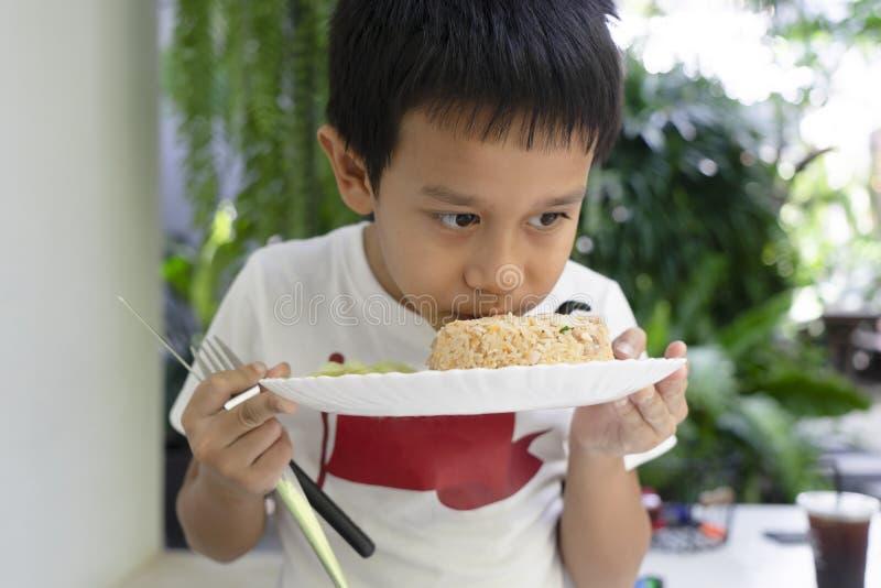 De asiatiska pojkarna luktar stekte ris med stor hunger arkivfoto