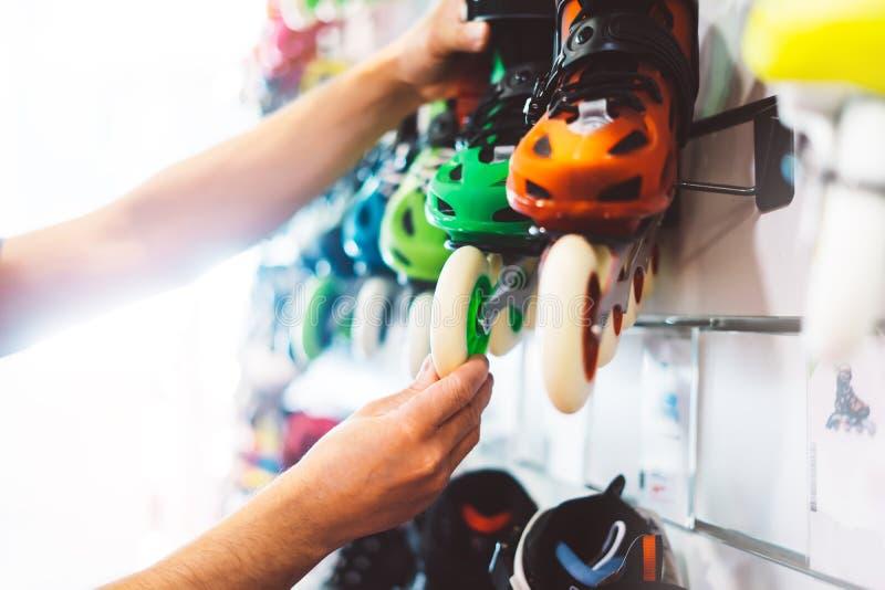 De assortimentsrolschaatsen in opslagwinkel worden geïsoleerd, persoon het kiezen en kopen kleurenrolschaatsen op de gloed die va royalty-vrije stock afbeelding