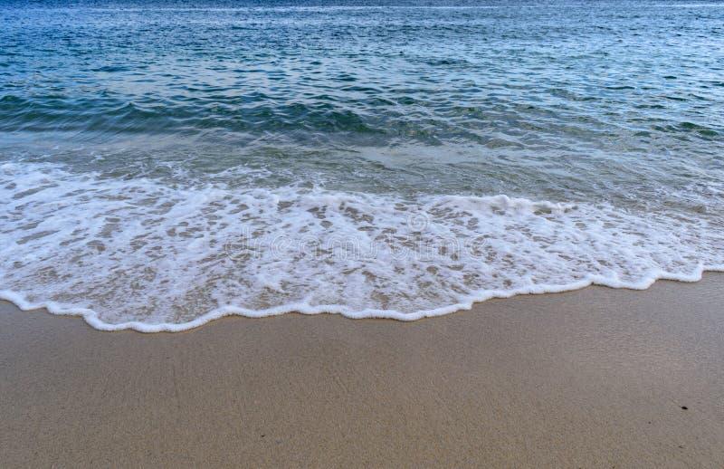 De Atlantische Oceaan - Blauwe overzees met golfschuim het uitspreiden in het zand na het busting royalty-vrije stock afbeeldingen