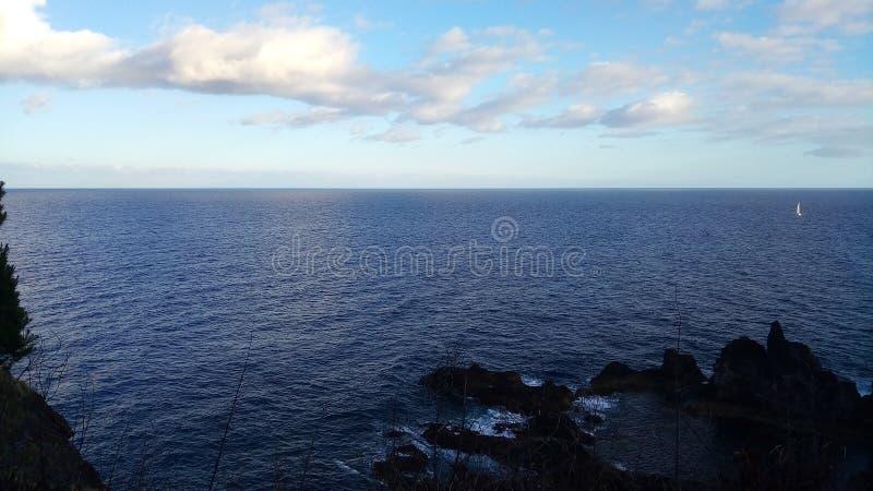 De Atlantische Oceaan en een kleine zeilboot bij het eiland van Madera, Portugal stock fotografie