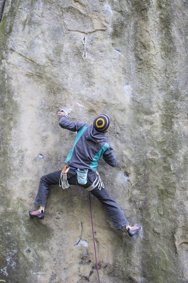 De atleet beklimt op rots met kabel stock afbeeldingen