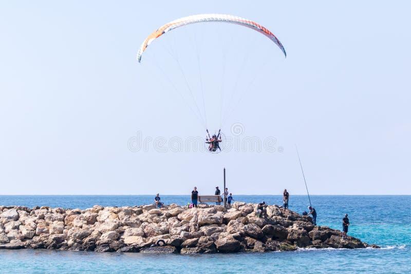 De atleet op een gekleurd gemotoriseerd valscherm vliegt in de loop van de dag stadsdijk van het Middellandse-Zeegebied in de Nah stock fotografie