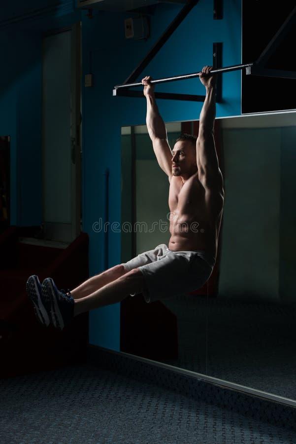 De atleet Performing Hanging Leg heft Oefening op stock foto's