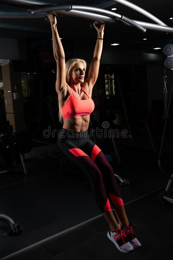 De atleet Performing Hanging Leg heft Oefening op royalty-vrije stock fotografie