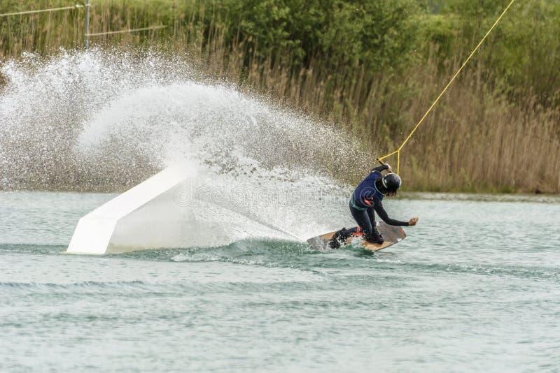 De atleet Woman is Wakeboarding bij het Kabelpark stock afbeelding