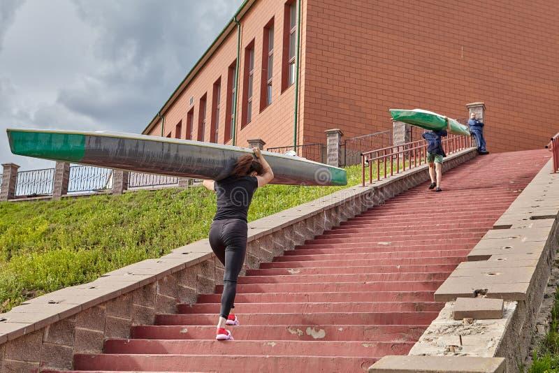 De atleten lopen boven met kajaks op schouders na het roeien tra royalty-vrije stock afbeeldingen