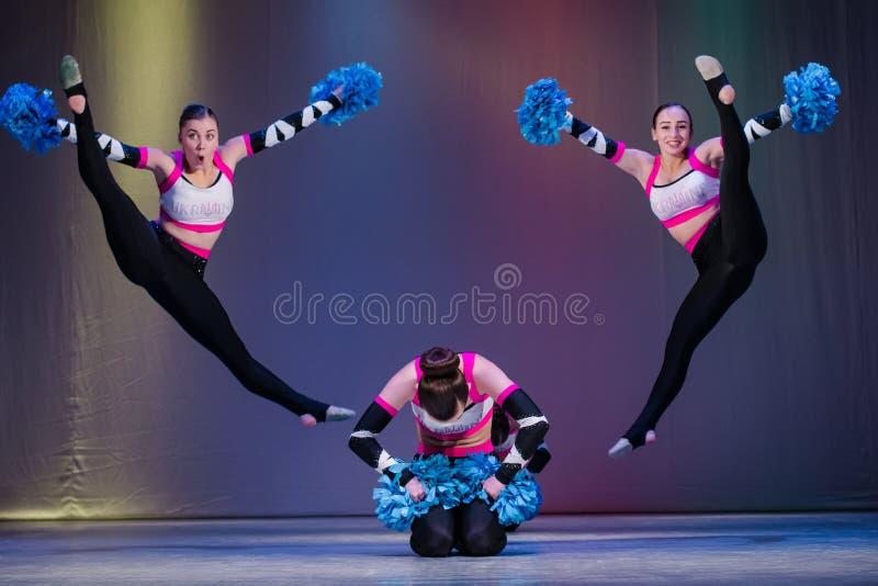 De atleten presteren op stadium, presteren jonge cheerleaders bij het cheerleading kampioenschap, meisjes in een sprong, meisje a royalty-vrije stock foto