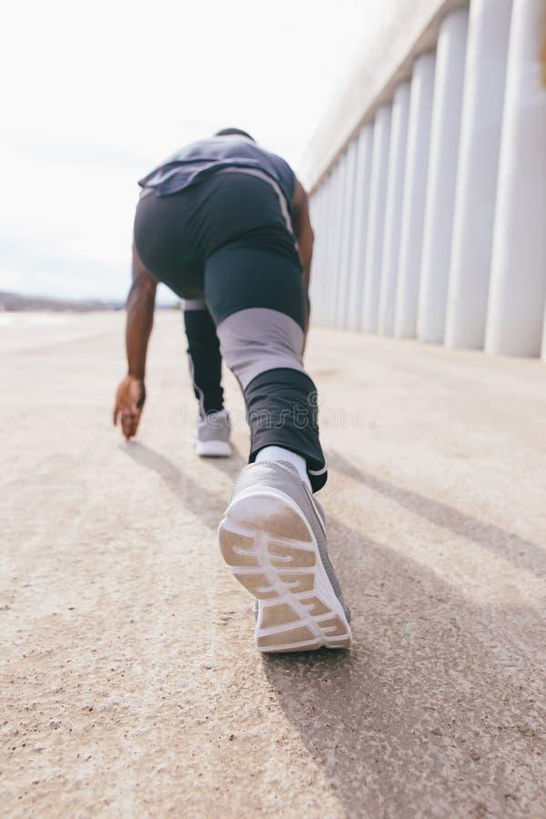 De atletenmens in het runnen van begin stelt op de stadsstraat Sport strakke kleren stock fotografie