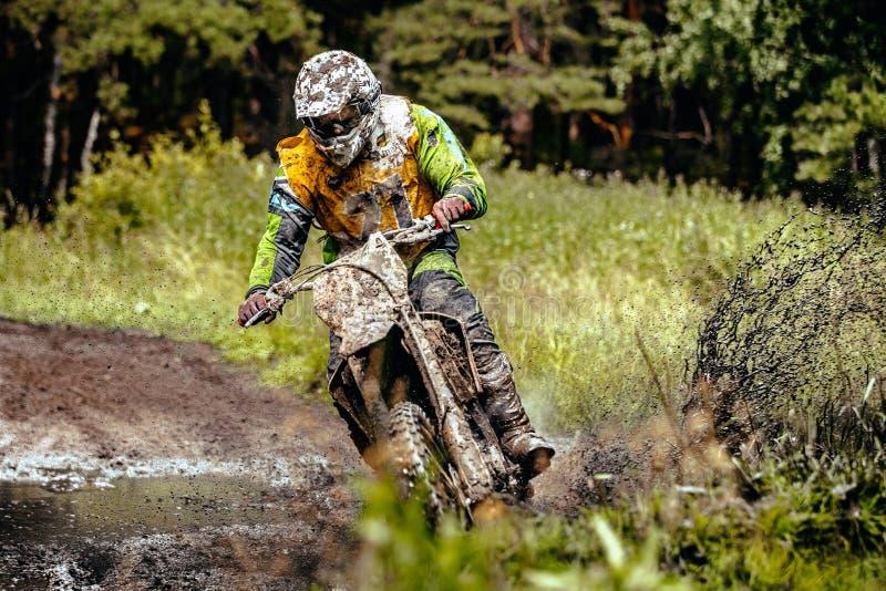 De atletenmotorrijder berijdt zijn fiets door een vulklei van modder in bos royalty-vrije stock foto's