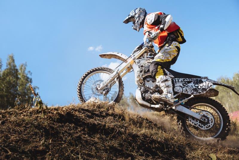 De atletenraceauto op een motorfiets berijdt omhoog heuvel op een stoffig spoor royalty-vrije stock foto's