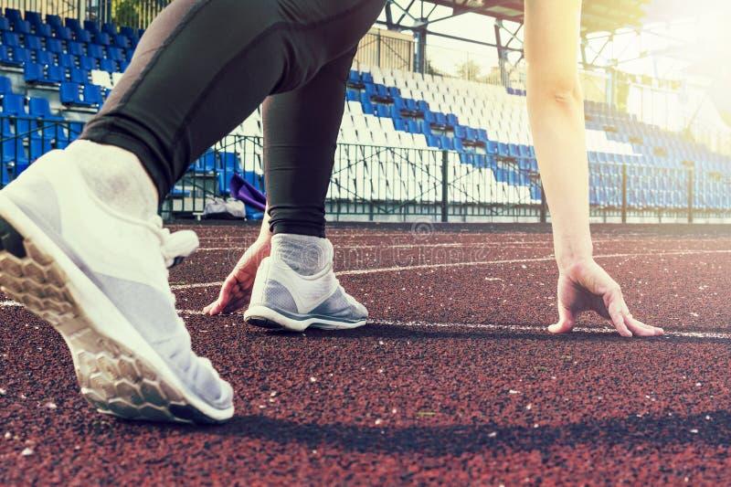 De atletenvrouw in het runnen van begin stelt op de stadsstraat Sport strakke kleren Sportenschoenen in de voorgrond, achtermenin royalty-vrije stock afbeelding
