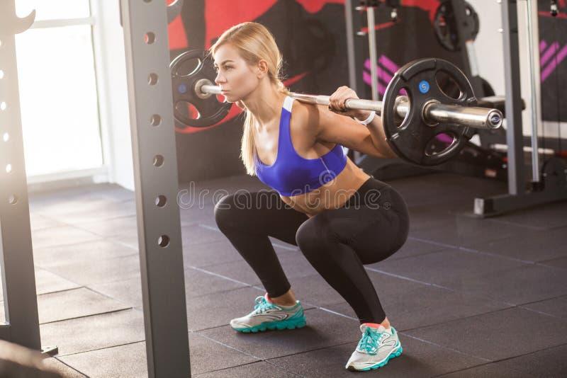 De atletenvrouw zit met harde bar stock afbeelding